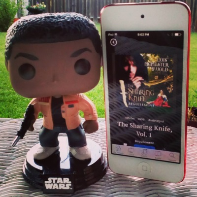 A large-headed Funko Pop bobblehead of Finn from Star Wars stands outdoors on a white wicker table. Beside him is a red-bordered iPod with The Sharing Knife: Beguilement's ugly cover on its screen. The cover features a hooded white man in the foreground, with a blonde white woman lounging on the ground behind him.