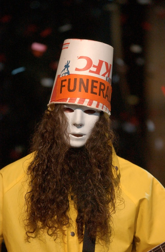 Buckethead trademark look: a KFC bucket, a Michael Myers Halloween mask, a yellow raincoat.