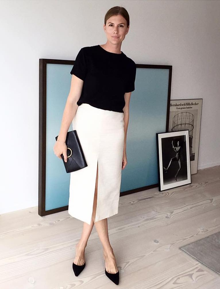 Polished Minimalist Spring Outfit Idea — Linn Hagglund instagram look with a black top, slit-front white skirt, and black mule heels