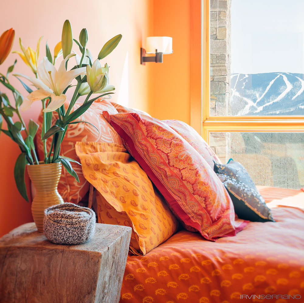 A residential bedroom filled with warmth and accented with reds and oranges overlooks the ski trails in the mountain region of Newry, Maine.
