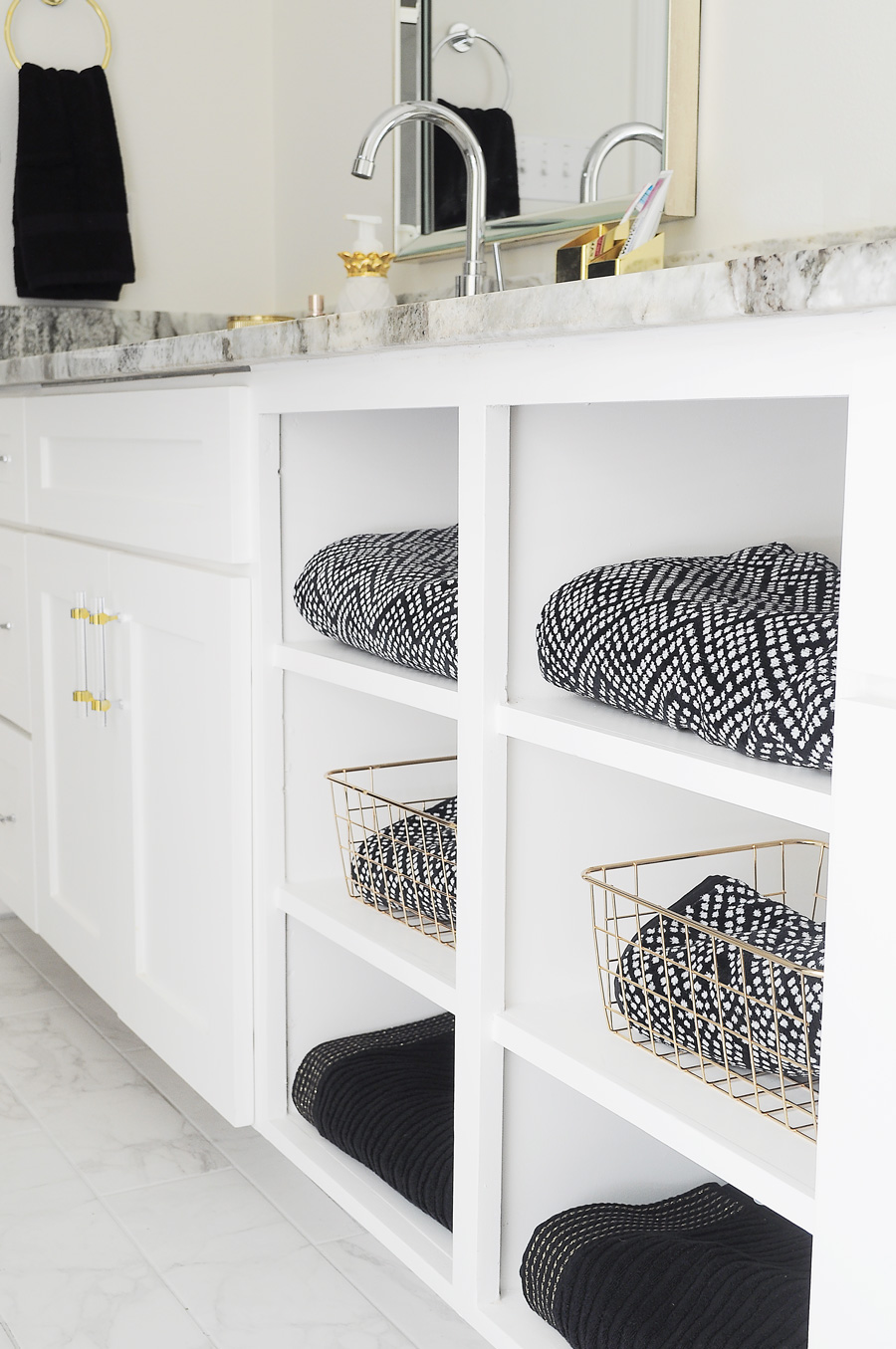 Black and white bath towels in open bathroom shelving.