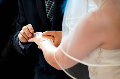 Hubby placing the rings on my fingers at our weding