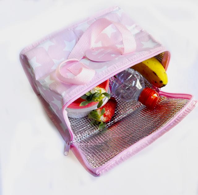 Bolsa termica de color rosa con estrellas blancas, sobre fondo blanco abierta en su interior hay frutas y un tupper redondo