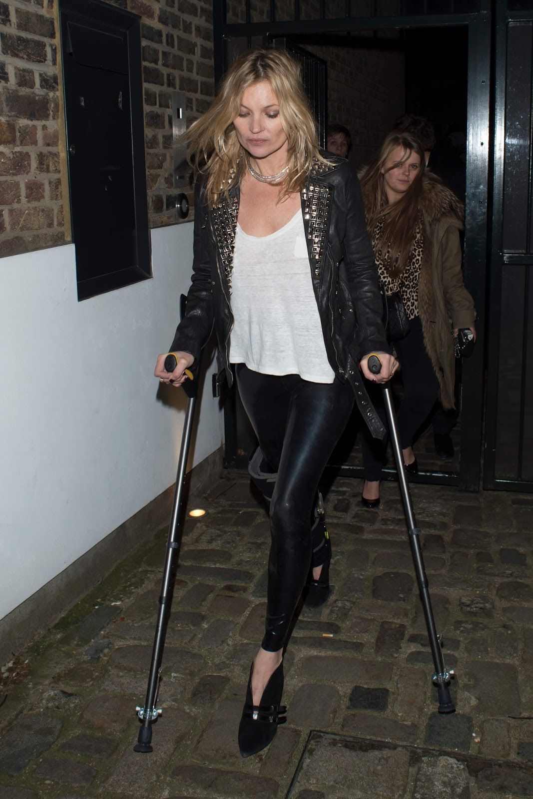706936a9dec419 British model Kate Moss wearing a black leather jacket with skin-tight black  latex pants (while on crutches):