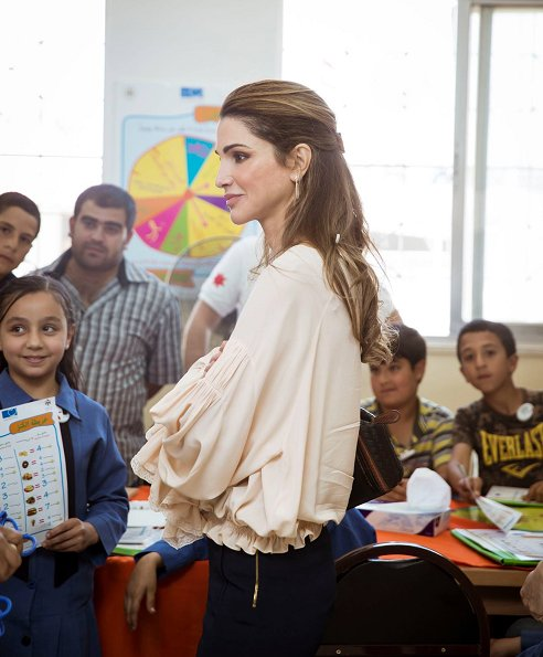 Queen Rania visited the Ballas Secondary School for Girls in Ajloun Governorate. Queen Rania style; wore Valentino blouse and Prada clutch bag