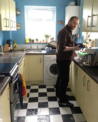 A man standing in a yellow kitchen with a black and white tiled floor