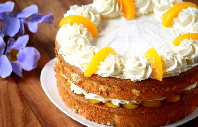 Torta de crema y duraznos sobre un plato blanco. flores lilas al costado izquierdo