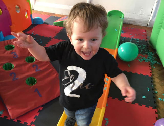 image shows toddler looking at camera and making a silly face