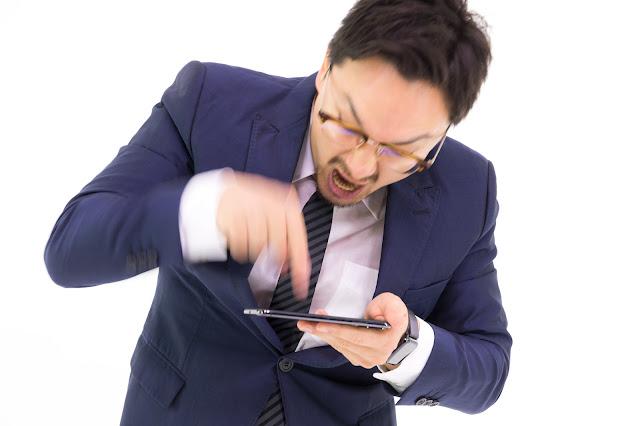 スマートフォンアプリを連打する男性