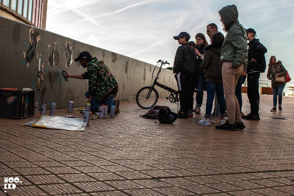 Belgian Street Artist Jaune at work on a stencil piece in Ostend, Belgium. Photo ©Hookedblog / Mark Rigney