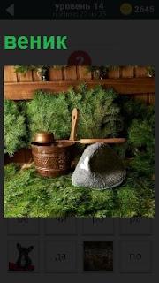 На полу в бане лежит веник, шапка и черпак для того чтобы подкидывать кипяток на камни