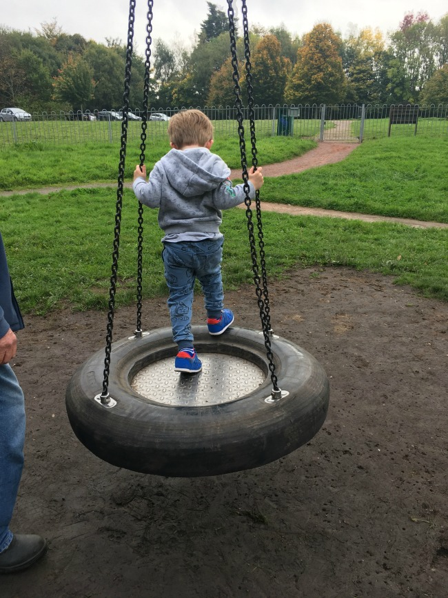 boy-standing-on-swing