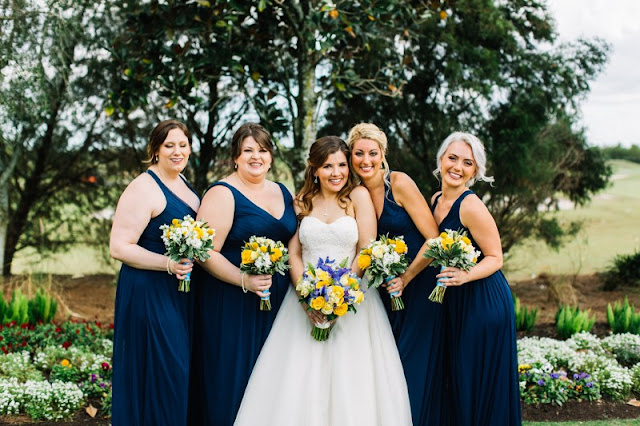 bridesmaids in long navy dresses with bouquets