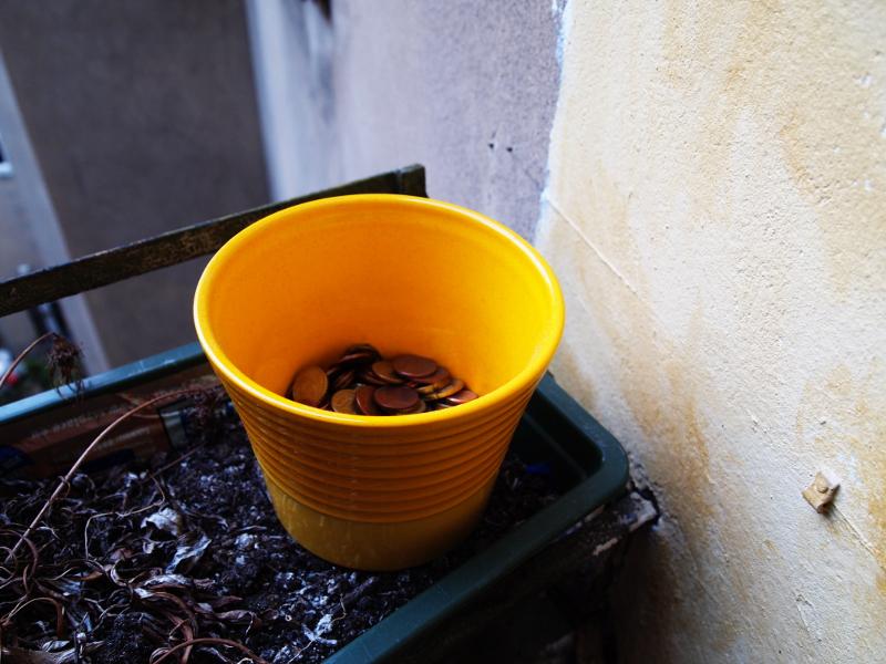 Gelber Blumentopf voller Kleingeld