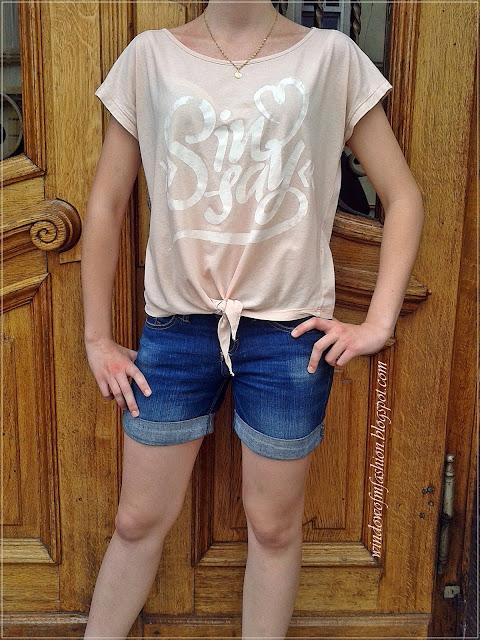Różowa wiązana koszulka, jeansowe krótkie spodenki, złoty medalik