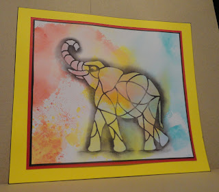 Elephant image with red, yellow, blue clouds behind, mounted don red and yellow