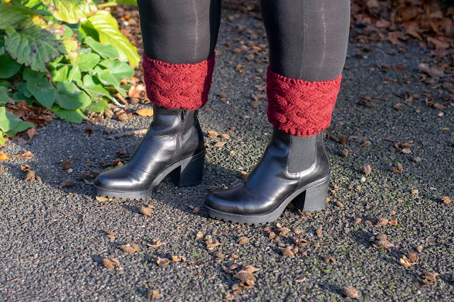 Black Chelsea boots with chunky heel and red ankle cuff with black tights on ground