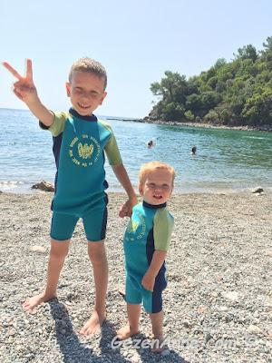oğlum ve bebeğim UV korumalı mayolarını giymiş kum plajlı Phaselis'te denize girerken, Tekirova Kemer Antalya