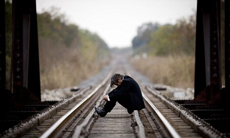 burrë ulur në shinat e trenit
