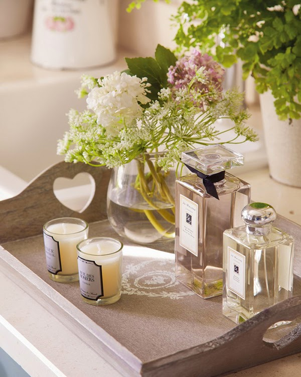 A tray of toiletries and scented candles on a shabby chic tray