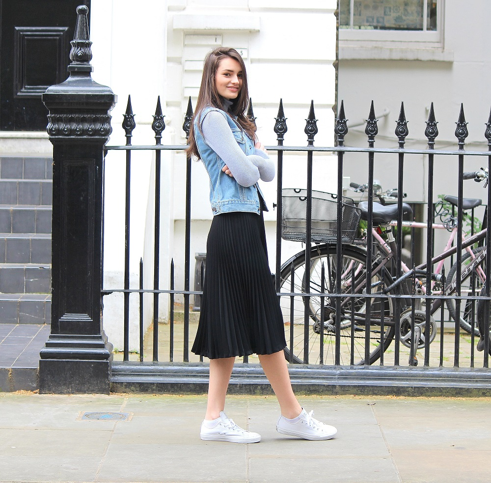 peexo fashion blogger wearing pleated midi skirt and roll neck top and denim vintage levis vest and converse in spring