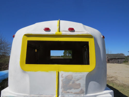 partially painted yellow and white fiberglass trailer