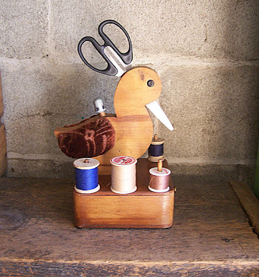 wooden bird holding scissors and thimble, with spools of thread at the base