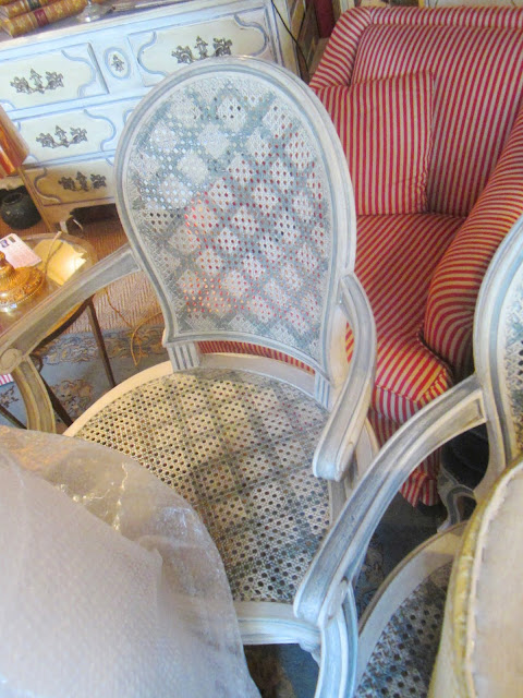 Close up of the grey painted trellis pattern on a white cane back armchairs