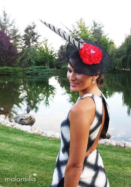 Invitada boda con vestido estampado geométrico en blanco y negro, tocado tipo plato en negro y flor rojo con plumas de faisán posando con escote en la espalda y un lago detrás