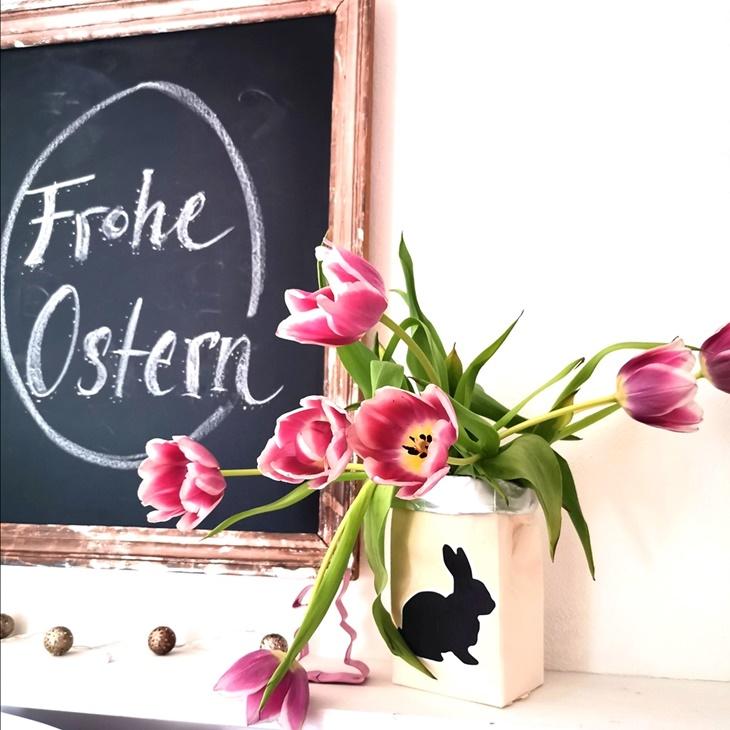 Osterdeko mit rosa Tulpen, weißer Tetrapack VAse und Tafelbild