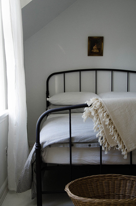 Bedroom with black iron bed and turkish blanket with tassels. Mur Lifestyle