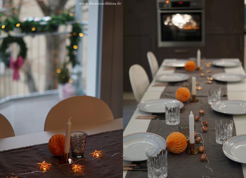 Die Tischdeko besteht aus einem simplen grauen Leinenläufer. Darauf stehen kupferne Kerzenleuchter, orangene Wabenbälle und grüne Facettegläser von Tine K. Trinkgläser von Nachtmann und batteriebetriebene Lichterketten vervollständigen das Bild.