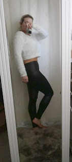 mirror selfie woman in white fluffy top and leather look leggings