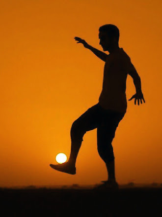 Güneşi bir futbol topu gibi saydıran ve ayağı üzerinde tutan sporcu