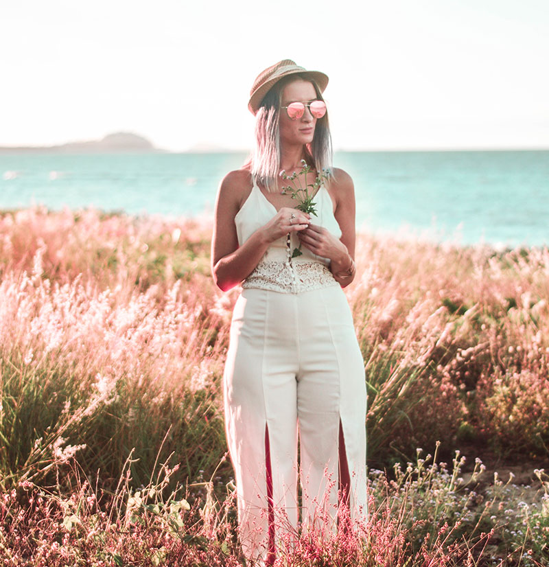 style inspiration australian blogger wearing boho white crochet jumpsuit with straw hat rose gold sunglasses stood in long grass field with sea in background