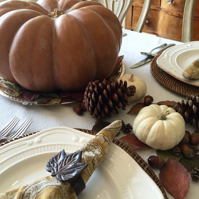 traditional fall tablescape with fairy tale pumpkin, pine cones and white pumpkins