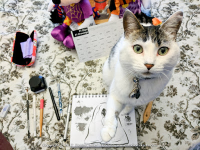 Mika's cat sitting on her Inktober drawing, reaching up to the camera.