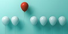 Ilmapalloja, punainen ilmapallo korkeammalla kuin valkoiset