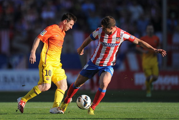 Atlético Madrid captain Gabi takes on Barcelona forward Lionel Messi