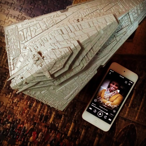 A shot from above of a bluetooth speaker shaped like a Star Destroyer. It sits atop a puzzle of a large crowd of people in early 18th century dress standing before some columns. Beside it is a white iPod with the cover of Yes, Chef on its screen. The cover features a smiling black man.