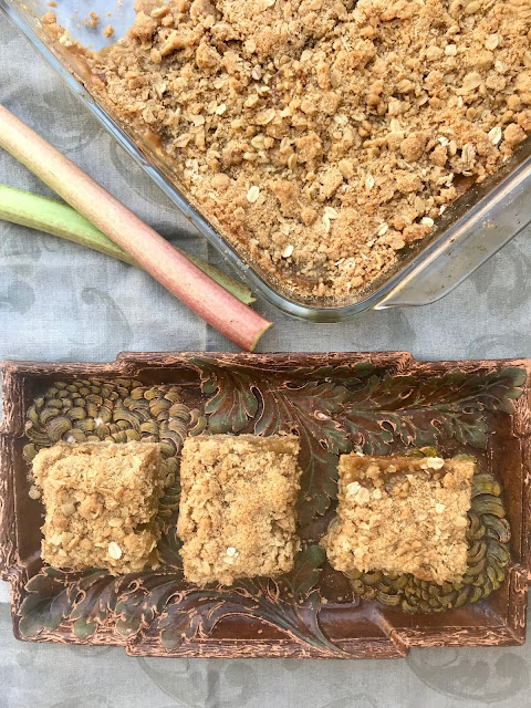 Finished rhubarb oatmeal bars along with three cute squares on a plate.