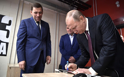 Vladimir Putin signs a hockey stick during his visit to the Datsyuk Arena sports complex.
