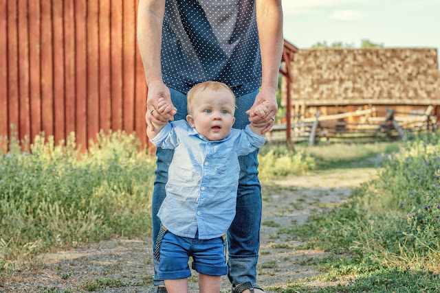 a baby boy walks along with his mother for their family's portrait session in Golden, Colorado