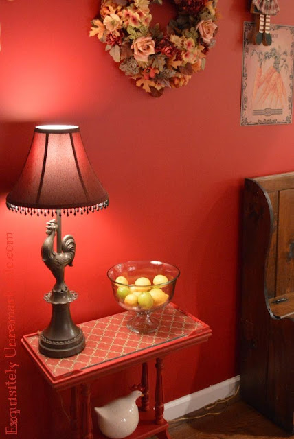A little red table with fabric under glass and a rooster lamp in the kitchen
