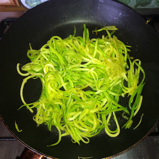 A serving of cooked zucchini pasta in a frying pan