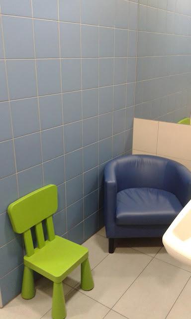 Pokój dla matki z dzieckiem Designer Outlet Gdańsk, w pokoju znajduje się fotel, krzesełko dla większego dziecka, przewijak, dwie toalety, umywalka.