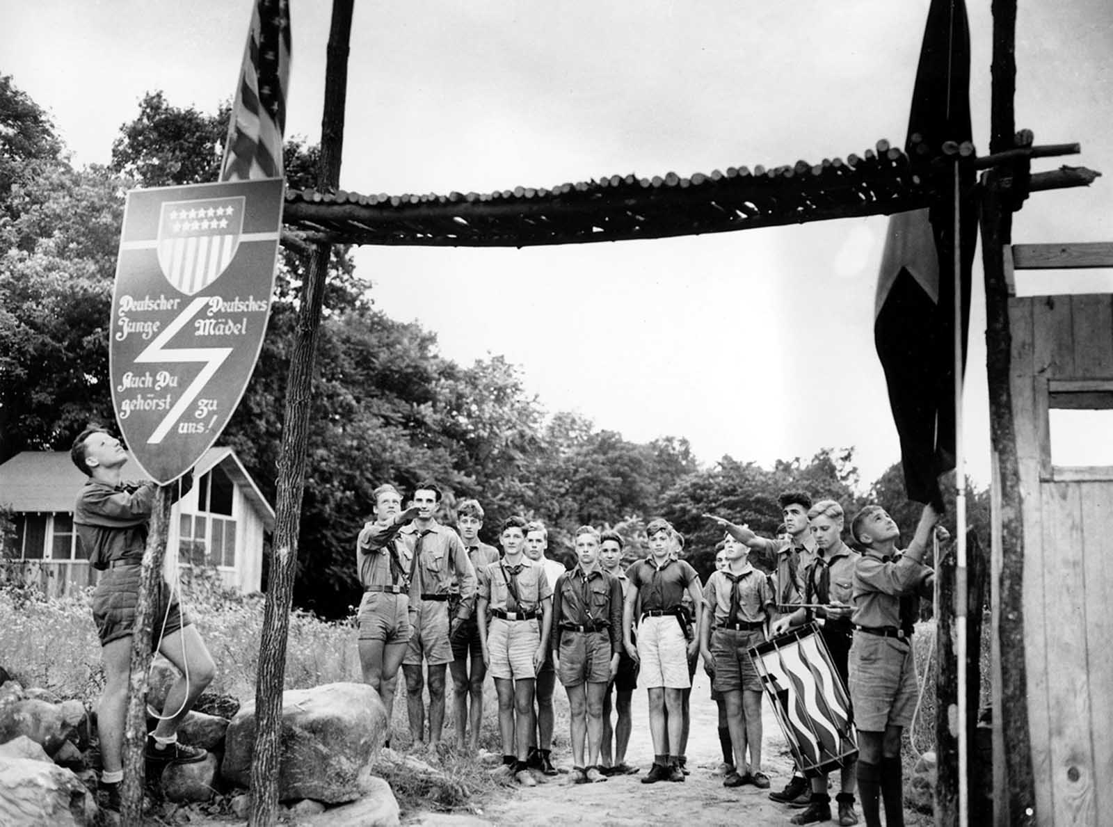 Youths at a German-American Bund camp stand at attention as the American flag and the German-American Youth Movement flag, right, are lowered in a ceremony at sundown in Andover, New Jersey, on July 21, 1937.