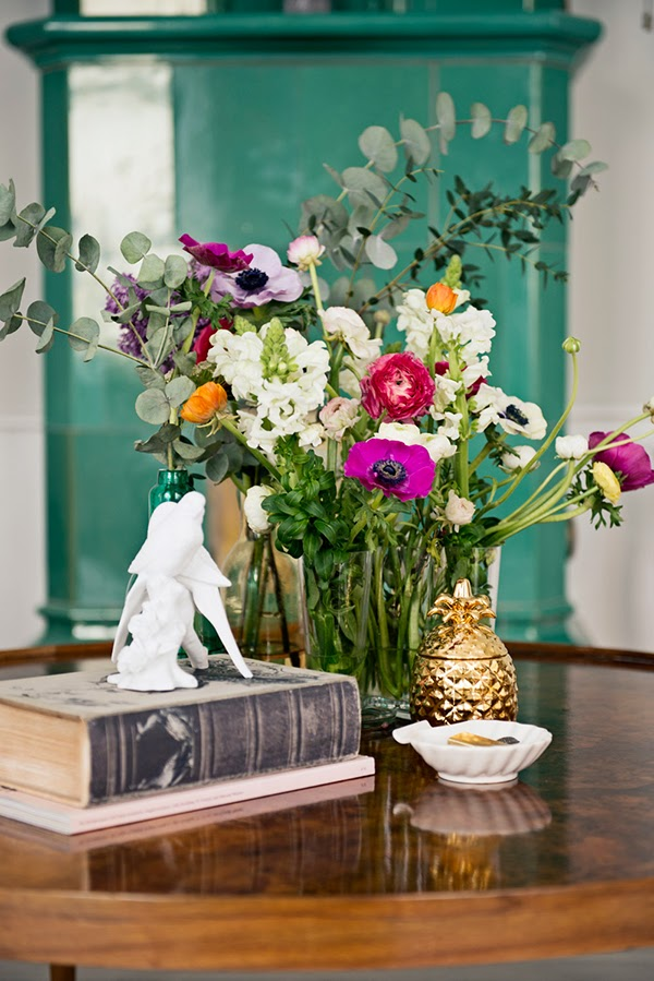 A bouquet of flowers in front of a teal green fire place