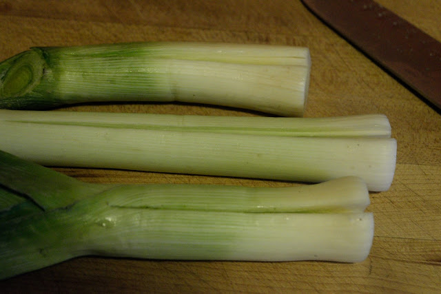 The leeks, on the cutting board, cut in half.