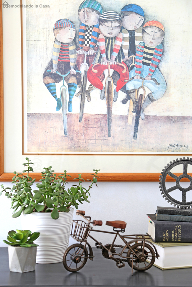 bike art with succulents and books on shelf - how to hang picture art
